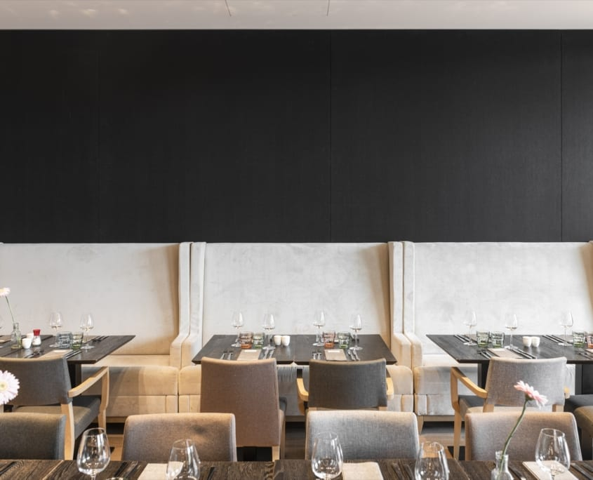 Nicely set tables with black wall panels in the restaurant of the Mercure Hotel