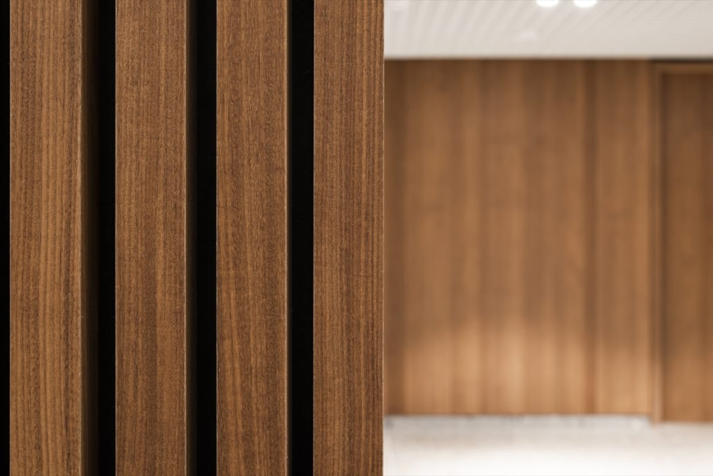 Detail acoustic wall with dark veneer slat wall